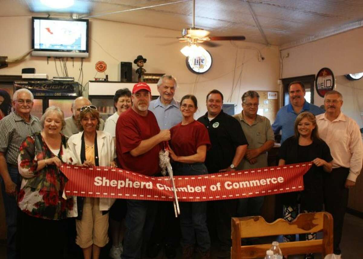 Gary Cash (left) and Della Cash (right) cut the Shepherd Chamber of Commerce ribbon, signifying Della's Pizza Kitchen becoming the chamber's newest member.