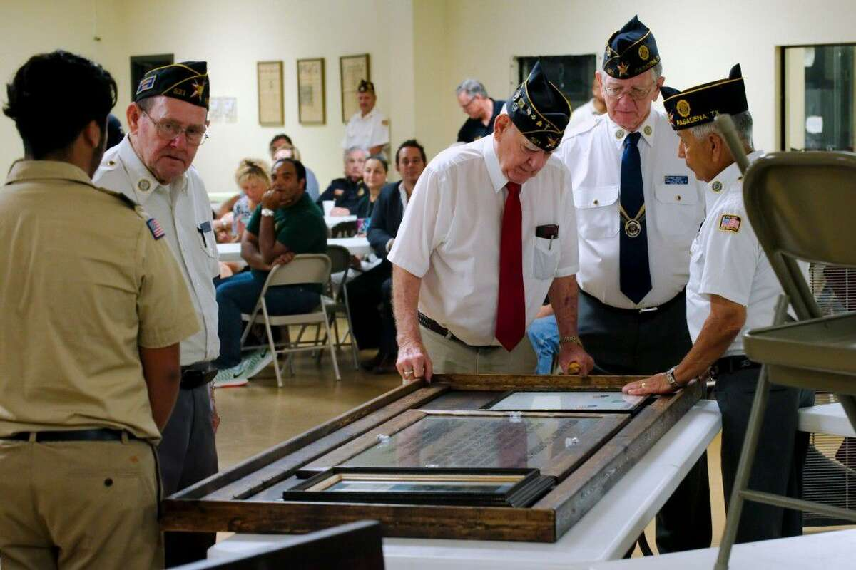 American Legion post members stand with Post 521 2nd Vice Commander Roy Maurer, inside left, who chats with Eagle Scout Christian Resendez after Resendez presents his Eagle service project, a plaque honoring the 1988 Post 521 Memorial Team of which Maurer is a founding member Sauturday, Aug. 13.