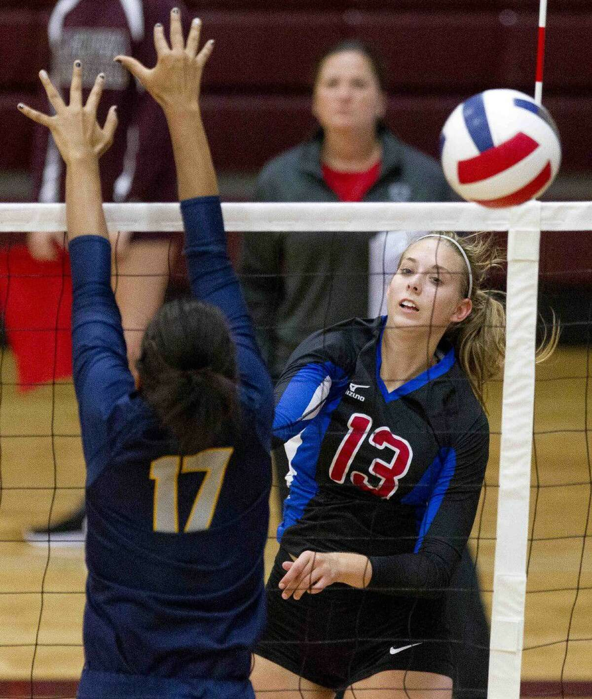 Oak Ridge's Brooke Clark gets a shot past Cypress Ranch blocker Kayla Benton during a match agaisnt Cypress Ranch at the Magnolia Volley-Battle tournament Friday at Magnolia High School. Go to HCNpics.com to purchase this photo and other like it.