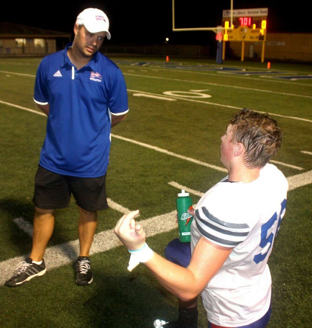Walker Draeger explains to head coach Justin Larsen what happened after Hull-Daisetta scored its first touchdown of Thursday's scrimmage in Hardin.