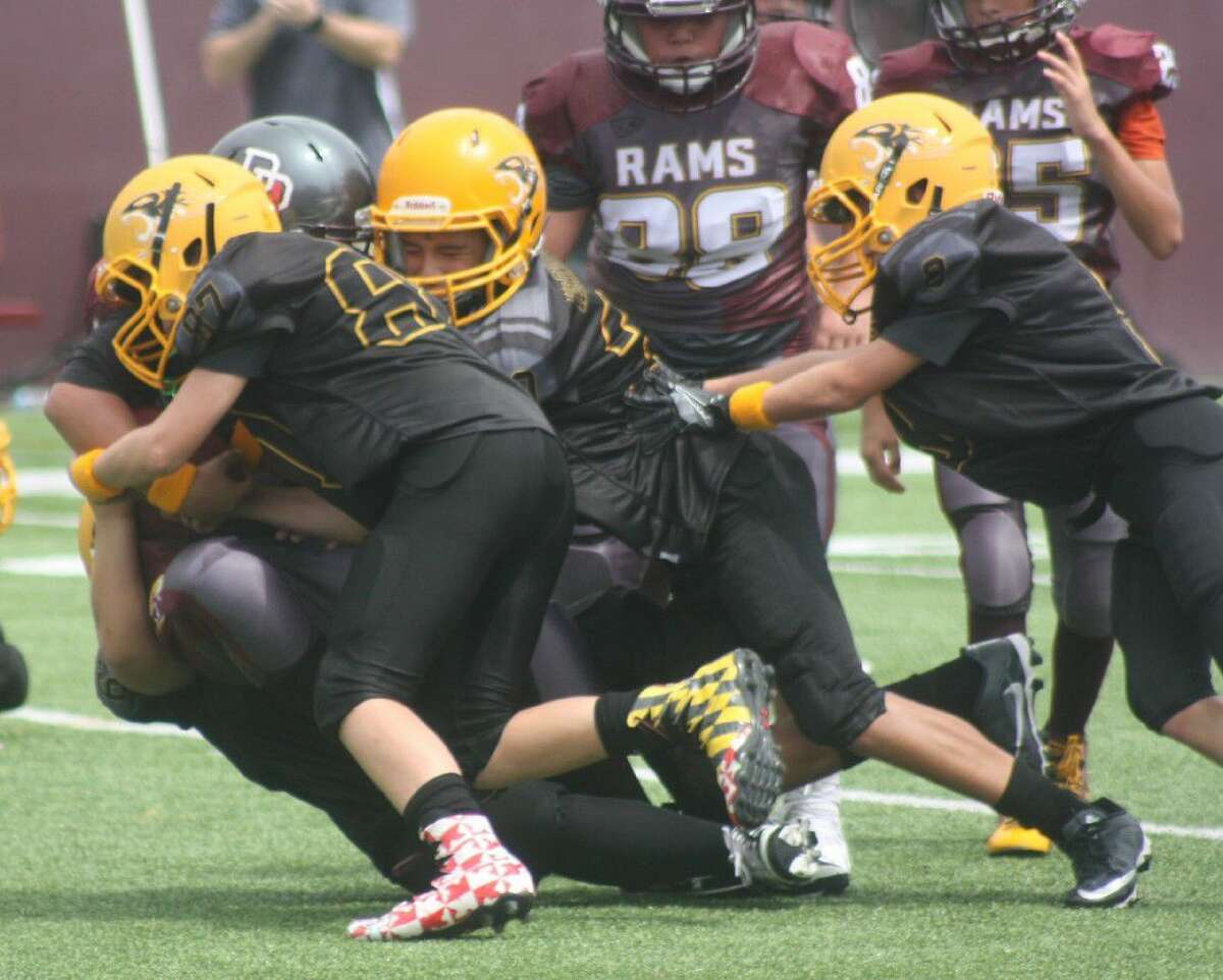 The Tigers defense smothers a Rams ballcarrier during Saturday's 14-0 Tigers victory at Abshier Stadium.