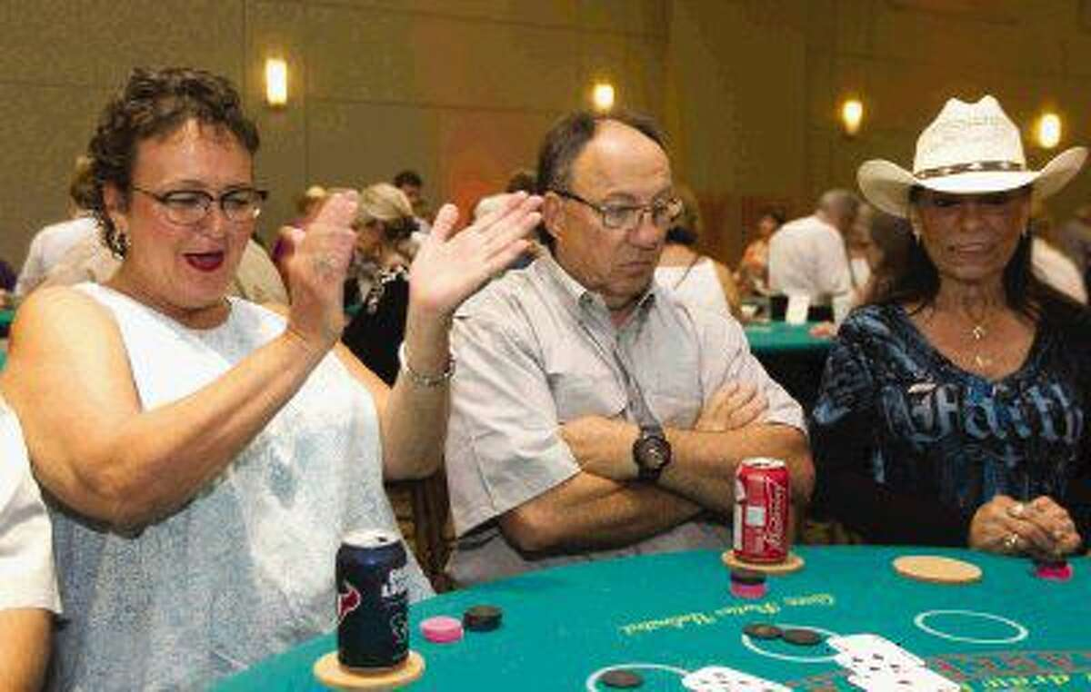 Debbie Terrell, left, celebrates winning a hand of blackjack while Joe James and Sissy O'Farrell were less fortunate during the annual Montgomery County Fair and Rodeo appreciation dinner Saturday at the Lone Star Convention & Expo Center.
