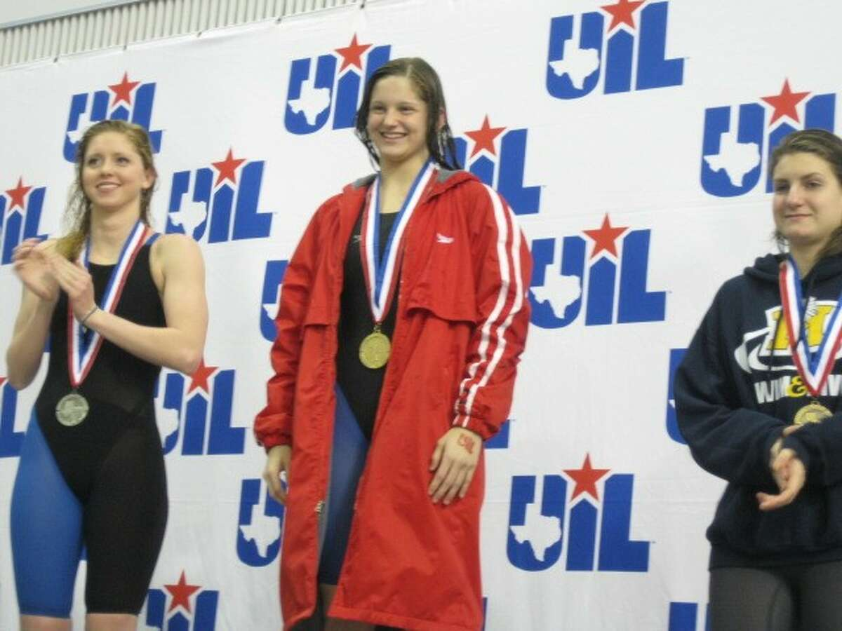 Memorial senior Alex Buscher stands on the medal podium proudly wearing her gold medal after she won the 5A state championship in the 200-yard freestyle event Saturday at the UIL Swimming and Diving state championships in Austin.