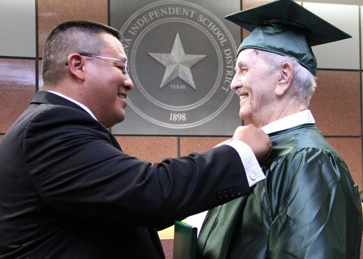 Pasadena High principal Joe Saavedra presents Korean War veteran Billy G. Williams with his PHS alumni pin.