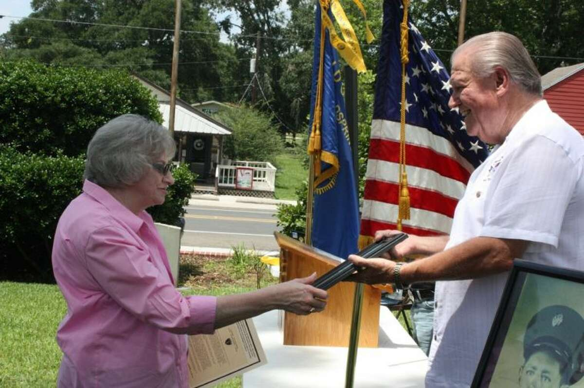 American Legion Post 629 First Vice Commander Dale Everitt (right) presents a plaque signifying the 70th anniversary of the D-Day invasion to Lanette Jackson (left), who is the niece of veterans Freelam and Truman Gilbert.
