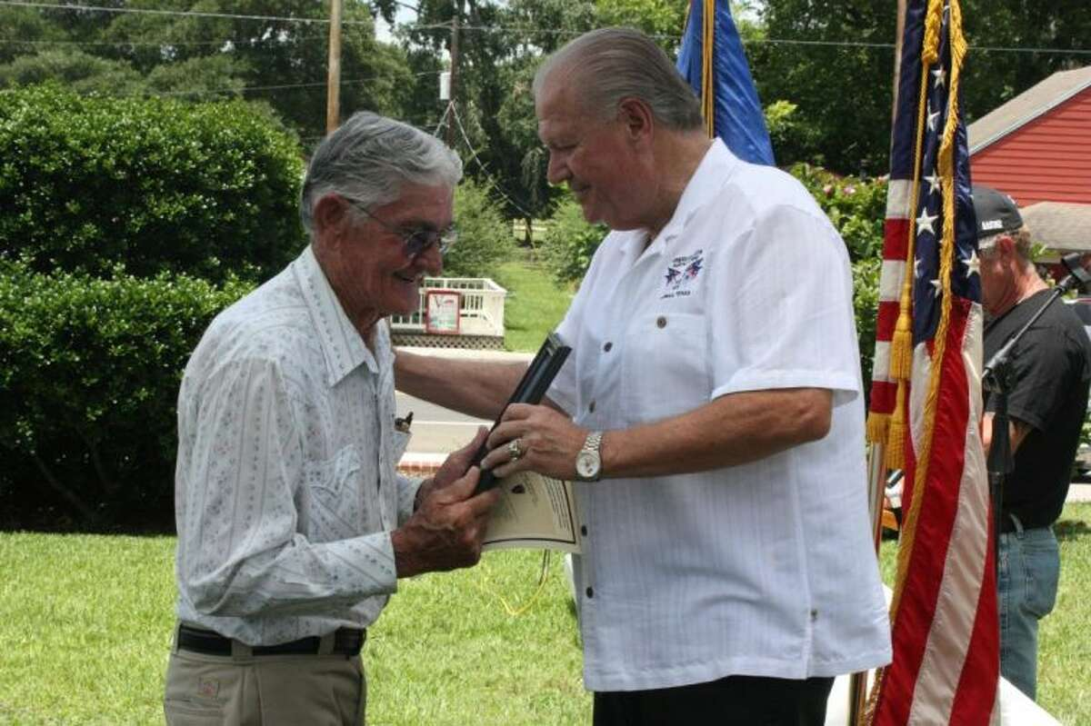 Leon Copeland (left) accepts an anniversary plaque in honor of his first cousin Clyde Copeland from American Legion Post 629 First Vice Commander Dale Everitt (right).
