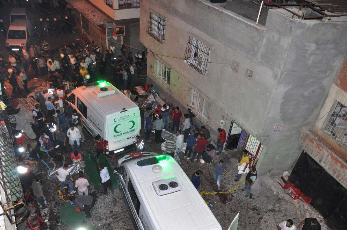 People carry dead bodies into ambulances after an explosion in Gaziantep, southeastern Turkey, early Sunday. A bomb attack targeting an outdoor wedding party in southeastern Turkey killed several people and wounded dozens.