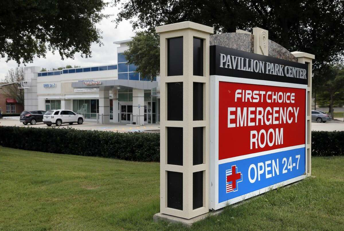 A sign by a nearby road intersection advertises a First Choice Emergency Room, rear, Thursday in Richardson, Texas.