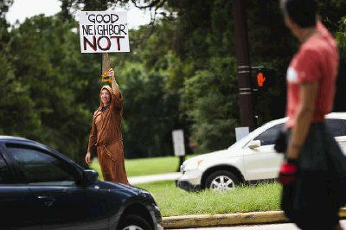 Will Burkholder, a resident of Laurelhurst Circle, carries a protest sign and dons a monk-inspired robe while demonstrating against St. Anthony of Padua Catholic Church Sunday at the intersection of Kuykendahl Road and Bay Branch Drive in The Woodlands. Residents near the church are dismayed at the clearing of trees along the greenbelt separating them from the church property.