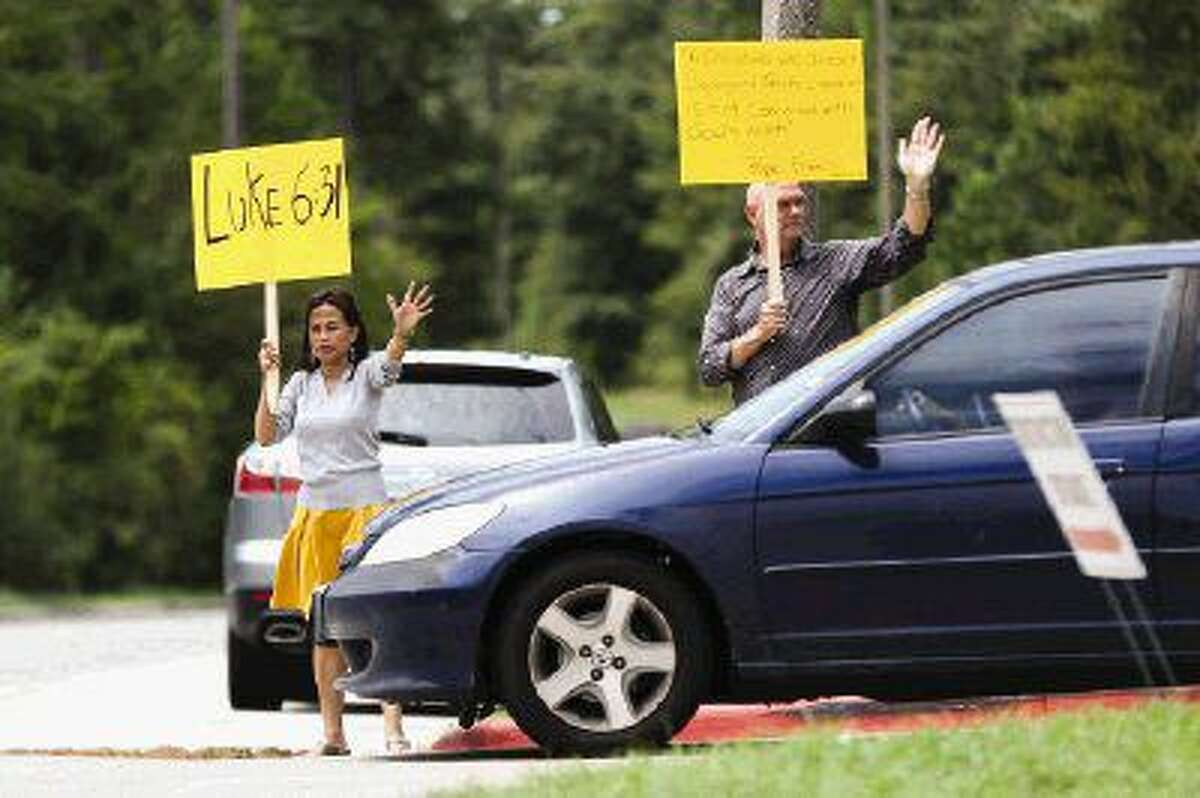 The Woodlands residents Kevin and Rini Rolens carry protest signs and wave at parishioners while demonstrating against St. Anthony of Padua Catholic Church Sunday. Although their homes are not affected by the tree clearing at St. Anthony of Padua Catholic Church, the Rolens came out in support of the residents because they believe this is an issue throughout The Woodlands.
