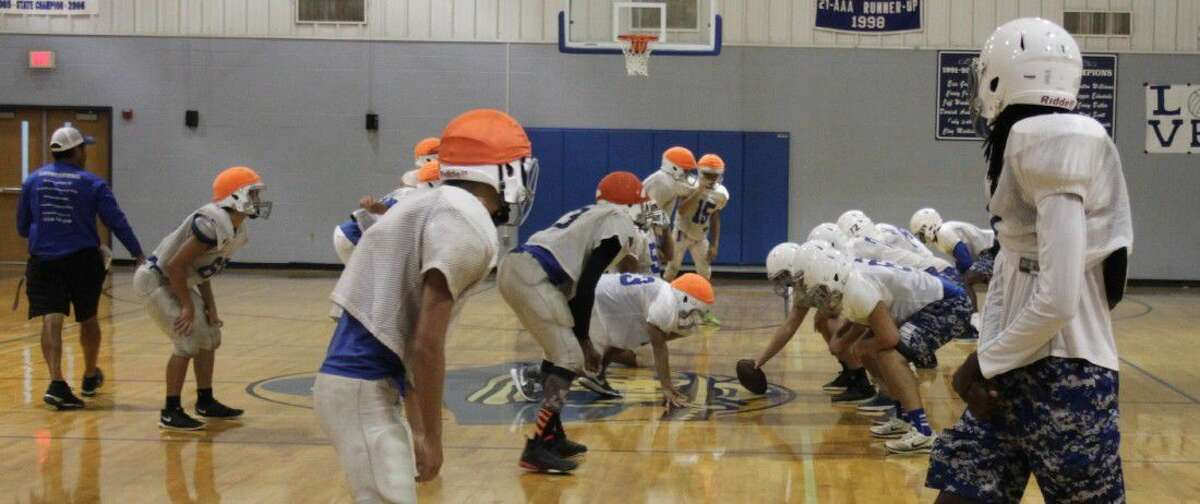 The Shepherd Pirates varsity football team practice their offense inside the Shepherd High School gym in order to avoid the rain during their two-a-day practices on Aug. 17.