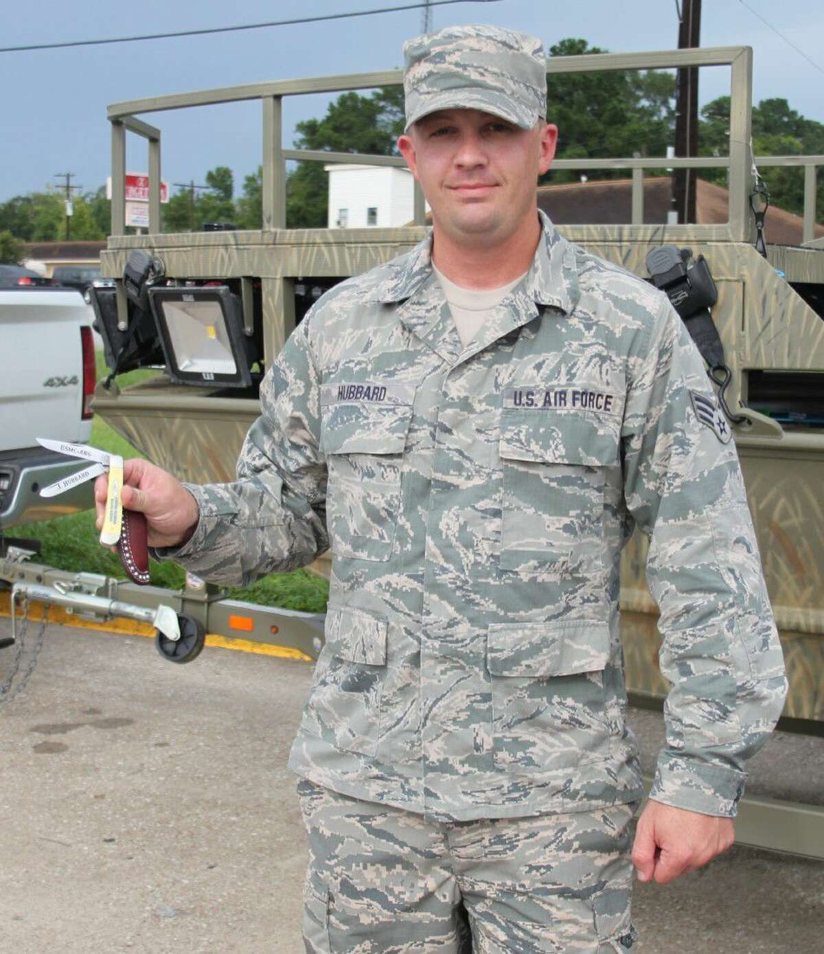Senior Airman Johnathon Hubbard of the United States Air Force is presented with an engraved knife as a gift from the Wicked Water Outfitters for his birthday. The knife bears the initials of the United States Marine Corp and the Air National Guard as well as his name.