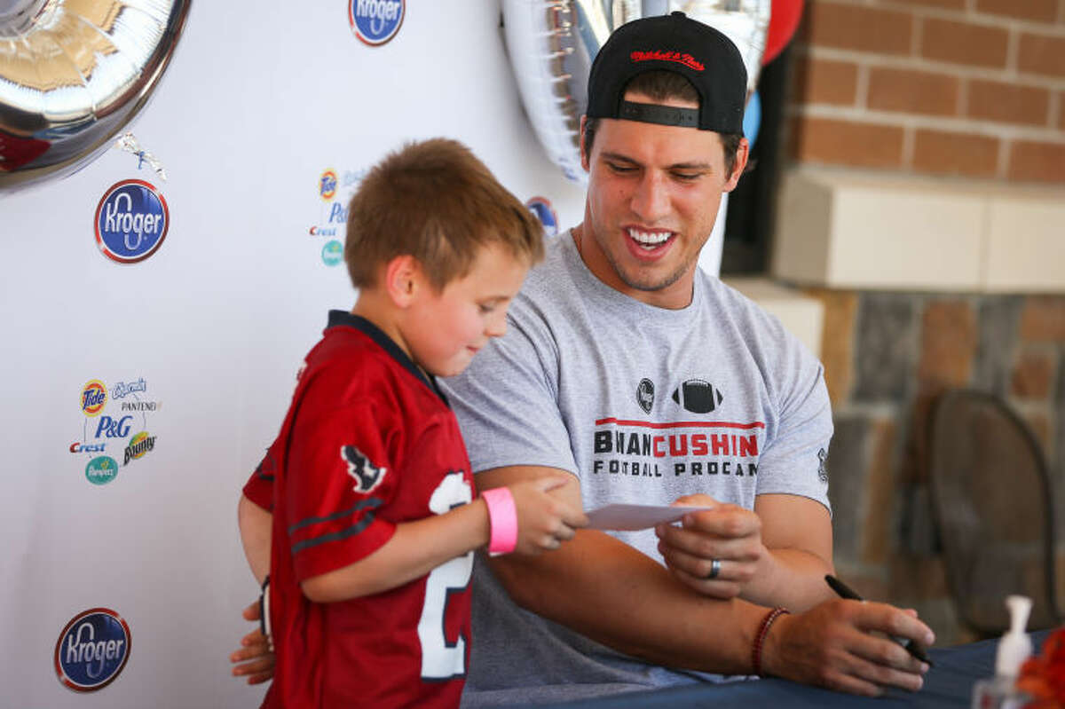Houston Texans linebacker Brian Cushing hands an autographed card to a fan on Saturday, May 3, 2014, at the Kroger Marketplace in Tomball.