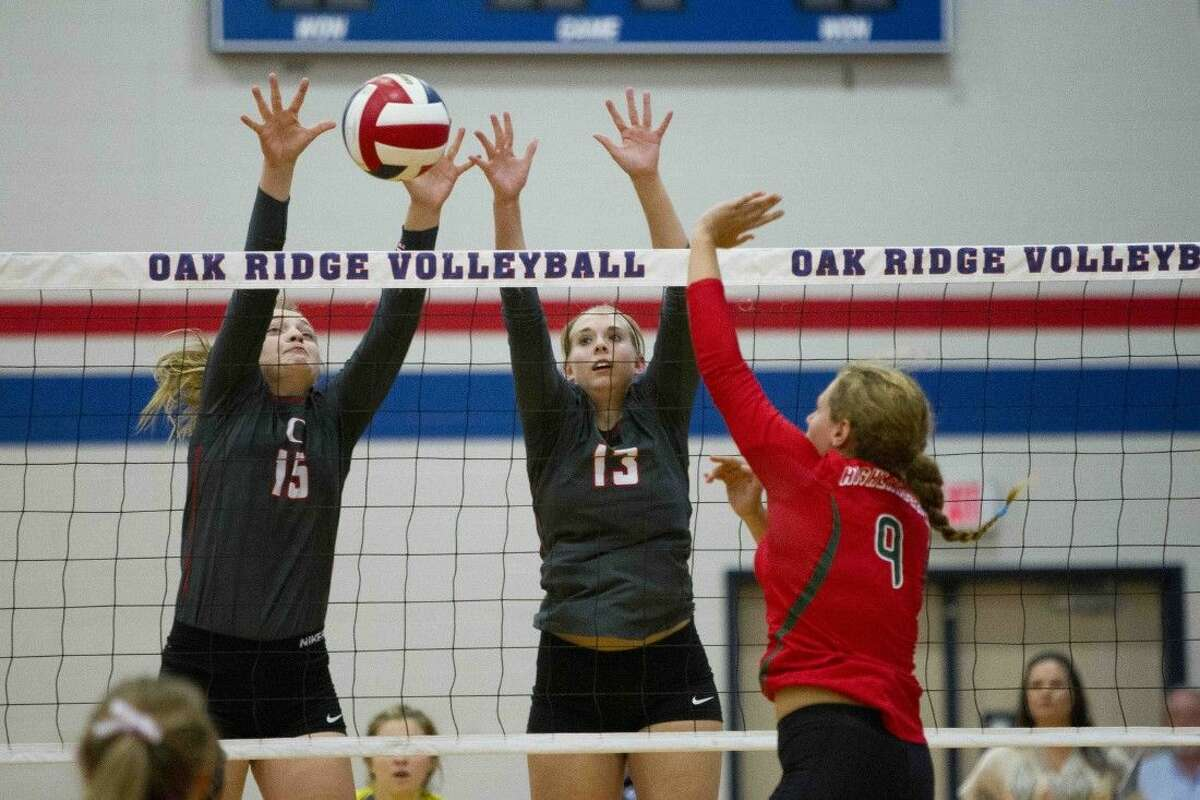 Oak Ridge's Hailey Lohnes, left, and Brooke Clark go up to block a shot by The Woodlands Grey Kennedy during a volleyball game Tuesday. To view or purchase this photo and others like it, visit HCNpics.com.