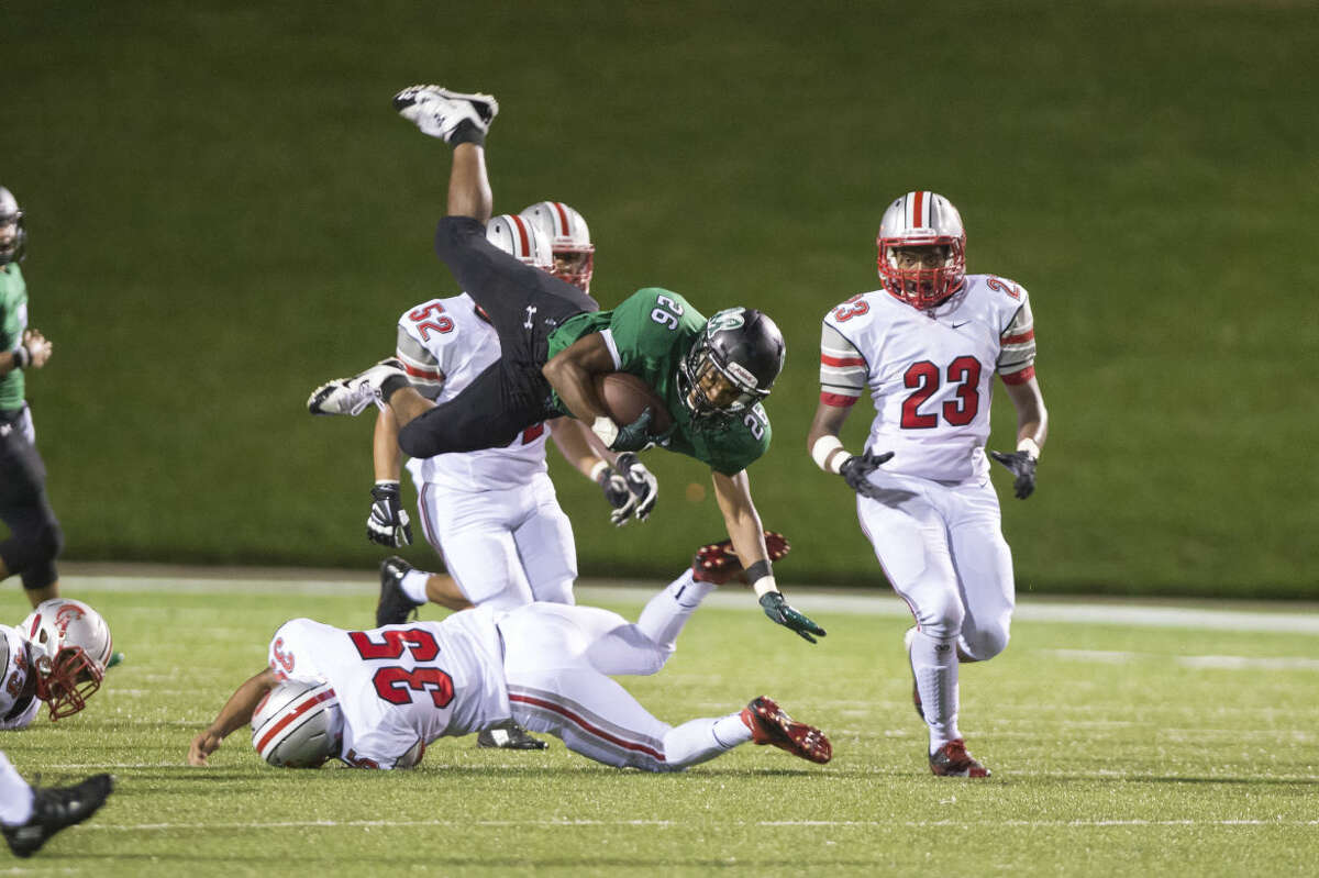 Mayde Creek's Donovan Lee is tackled by Cy Lakes' Blake Wheelwright (35) as Jude Keelen (23) and Alec Singleterry (52) converge Sept. 3 at Rhodes Stadium in Katy. Lee rushed for 326 yards and three touchdowns. To view or purchase this photo and others like it, visit HCNpics.com