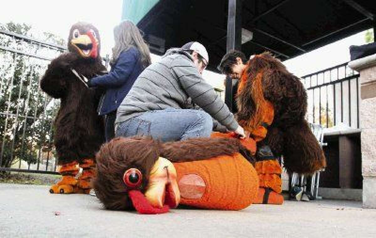 Caleb Vega, right, gets some help with a turkey costume from Josh Thorton as Kimberly Berriochoa makes some final adjustments to Max Garcia's costume before the annual Run Thru The Woods on Thursday near the Cynthia Woods Mitchell Pavilion.