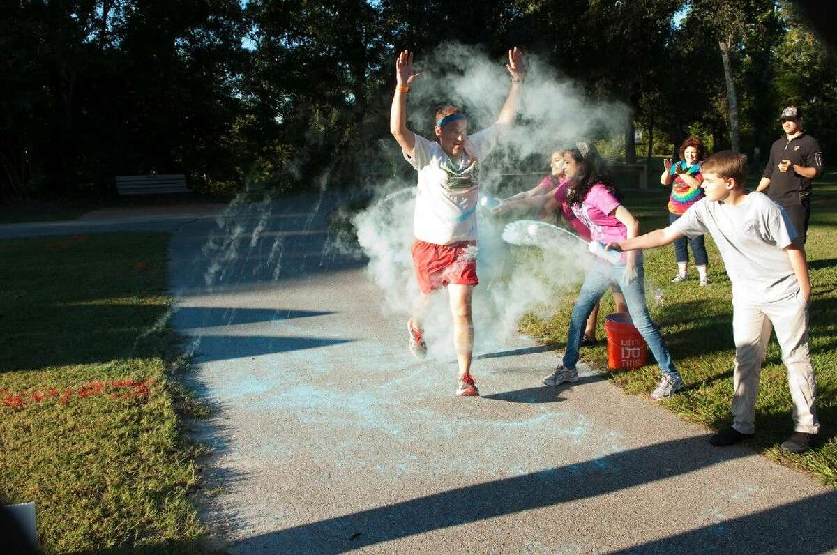 A runner is dowsed in color during the annual color run at last year's Creekfest celebration.
