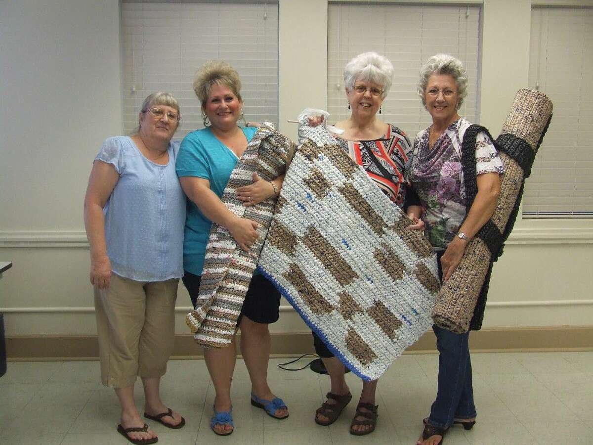 Tomball residents, from left, Fances Dobson, Ganeen Cron, LaVerne Meade and Wilma Flanakin show off the mats for the homeless their group has been working on at the Tomball Community Center on Tuesday mornings.