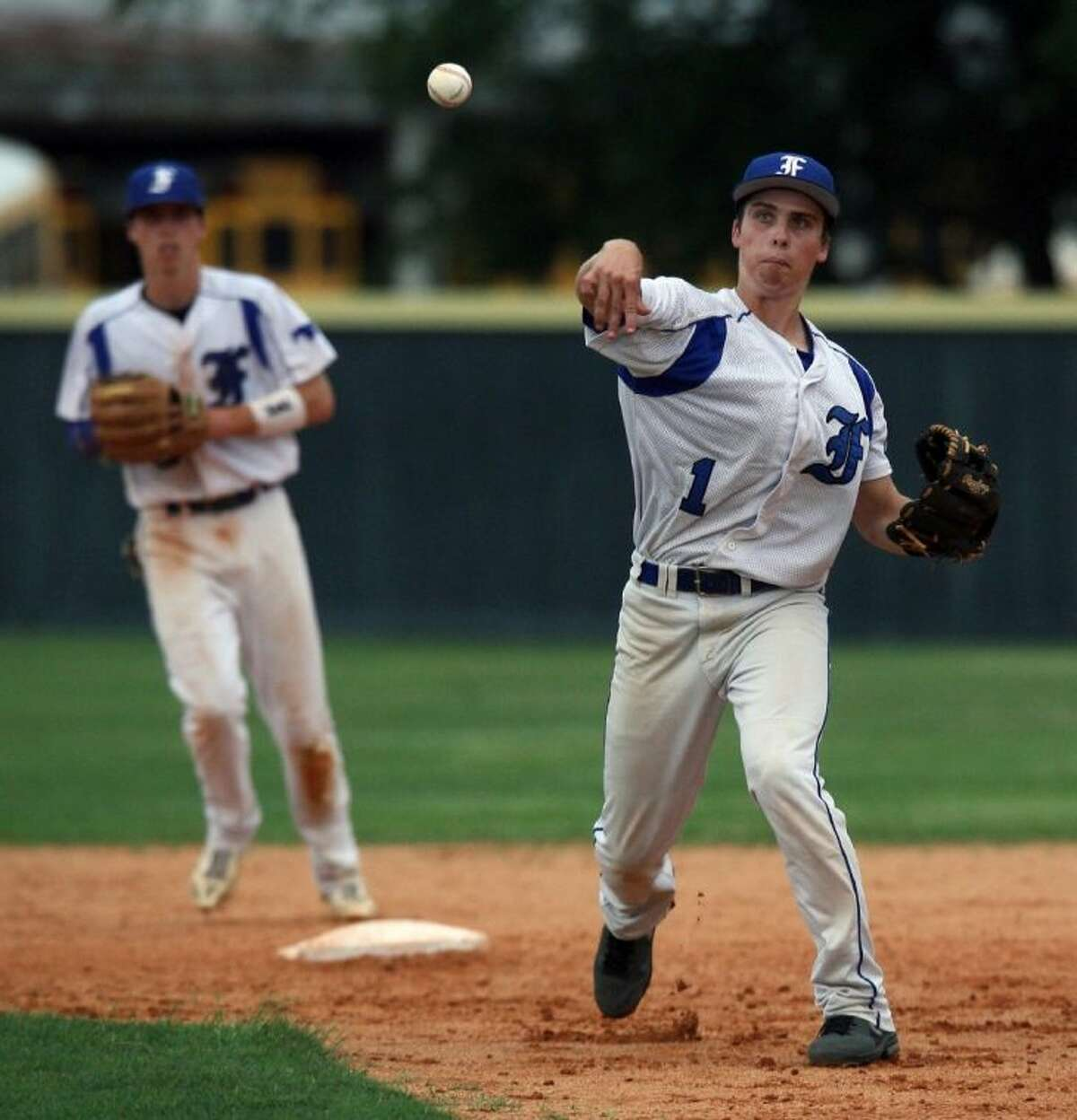 Friendswood's Jacob Gwynne throws to first for an out in the Mustangs' area-round playoff win over Houston Milby.