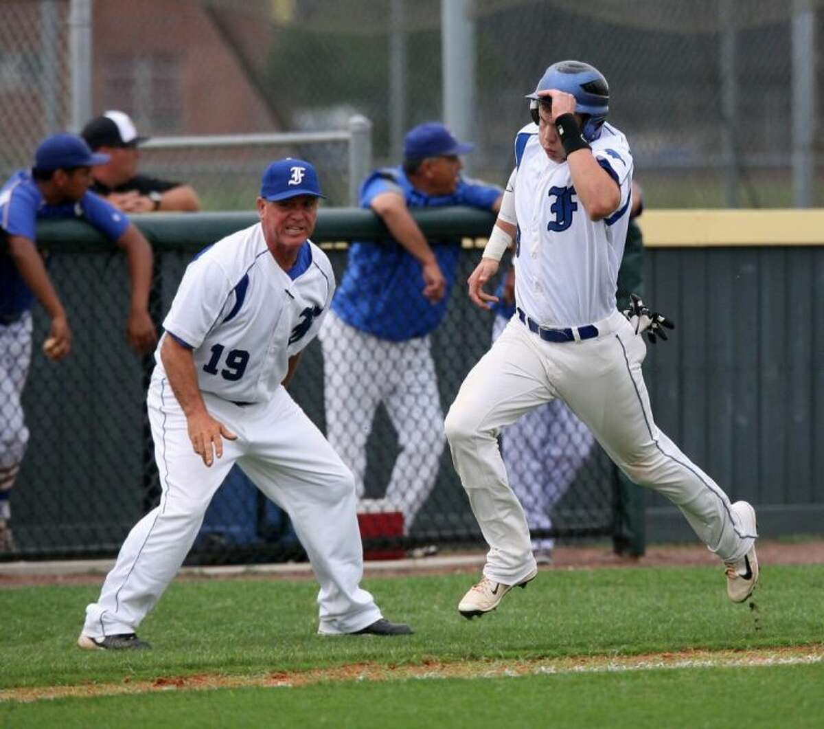 Friendswood baseball coach Charlie Taylor tells Walker Williams to get moving as he sends him to home plate Friday against Houston Milby.