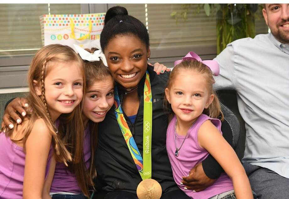 Simone Biles visited with Cicelia, Callie and Gianna Cacchione after her news conference and Saturday at Houston Methodist Willowbrook Hospital. The girls are the daughters of Cypress residents Marikathryn and Timothy Cacchione, who just welcomed their fifth child into the family. Photo: Tony Gaines