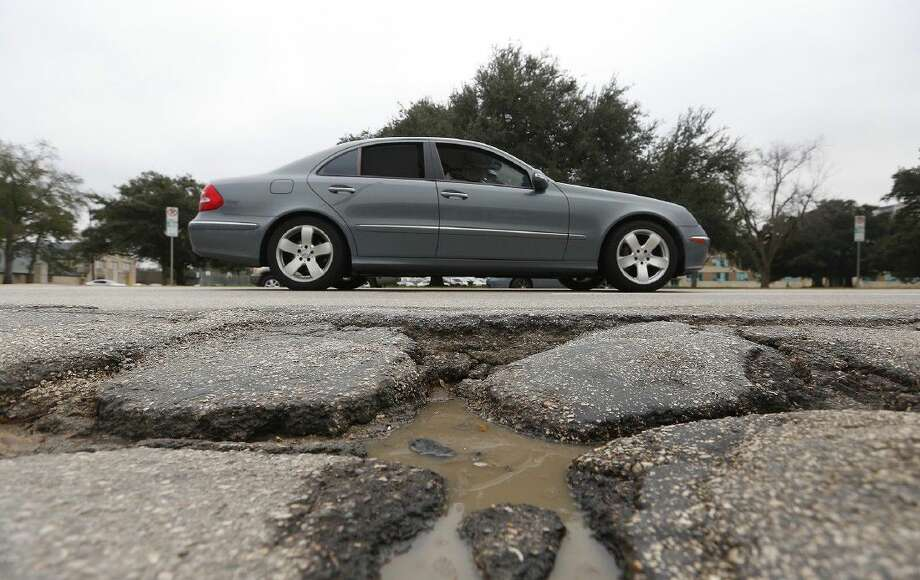 A driver makes their way past a pothole along Westheimer Road, near Eastside Street, Wednesday, Feb. 4, 2015, in Houston. Photo: Cody Duty