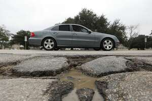 A driver makes their way past a pothole along Westheimer Road, near Eastside Street, Wednesday, Feb. 4, 2015, in Houston.