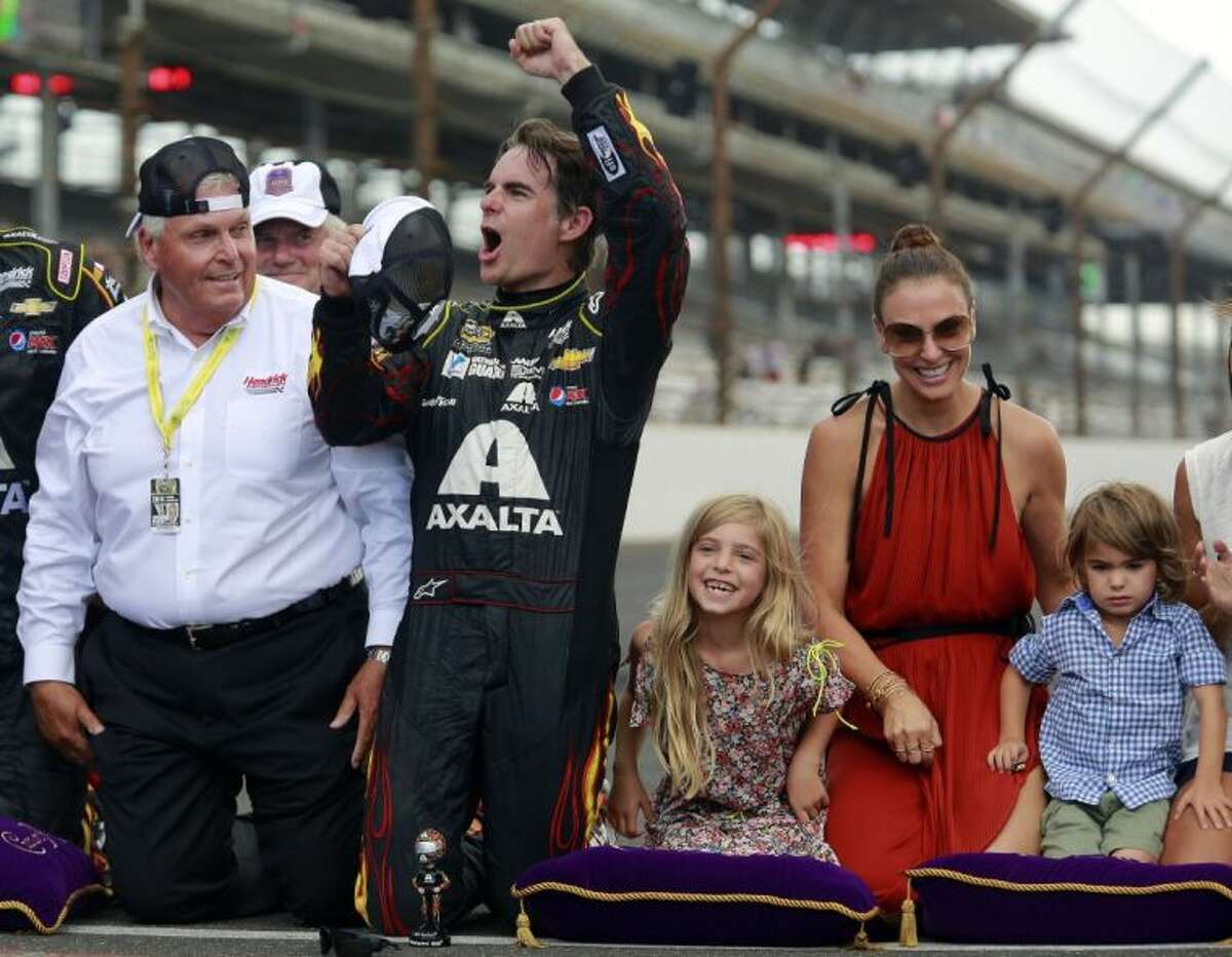 Jeff Gordon celebrates after winning the NASCAR Brickyard 400 auto race at Indianapolis Motor Speedway. At left is team owner Rick Hendrick. At right are Gordon's wife, Ingrid Vandebosch, and their children, Ella Sofia and Leo Benjamin.