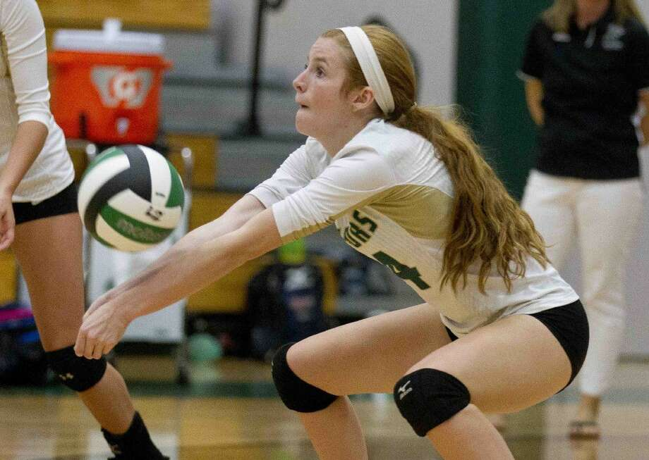 The Woodlands Christian outside hitter Macie Draudt (14) goes for a dig during the second set of a non-district high school volleyball match Tuesday. Go to HCNpics.com to purchase this photo and others like it.