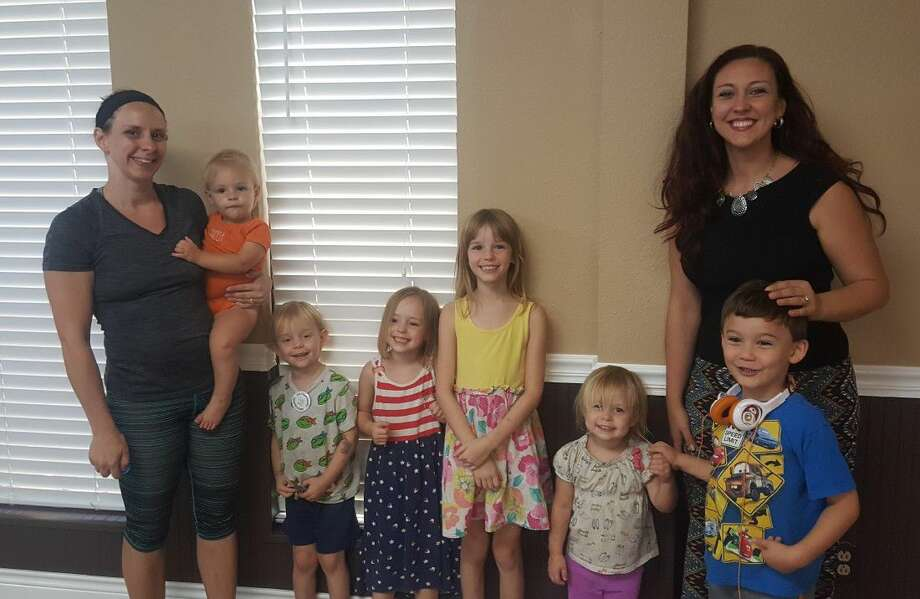 Roman Forest residents Sarah Novak and Samantha Costa pose with their young children after the Roman Forest town hall meeting where Roman Forest city council unanimously approved a splash pad agreement with EMCID Aug. 30.