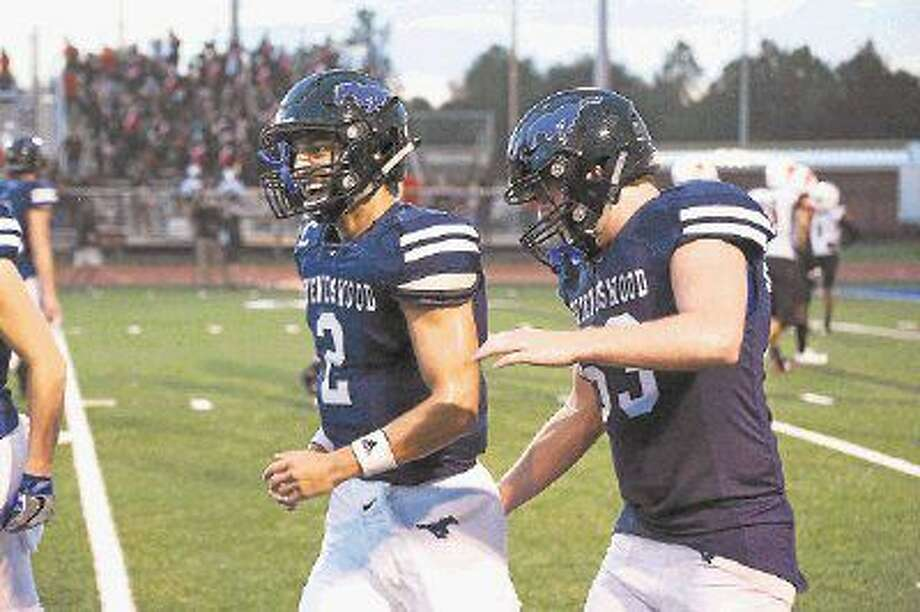 Friendswood quarterback Tyler Page (2) is congratulated by lineman Connor Stanford (53) Friday in the Mustangs' 54-20 win over Texas City. Page accounted for seven touchdowns while Stanford recovered a fumble for another TD. Photo: Kirk Sides