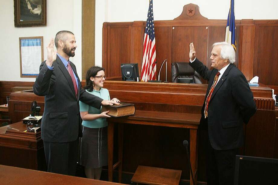 Poston, with his left hand on the Bible, raises his right hand to take the oath of office delivered by The Honorable Mark Morefield in the 75th District Courtroom in Liberty, Texas on Thursday, Sept. 1. Holding the Bible is Poston's wife, Mary. Photo: David Taylor