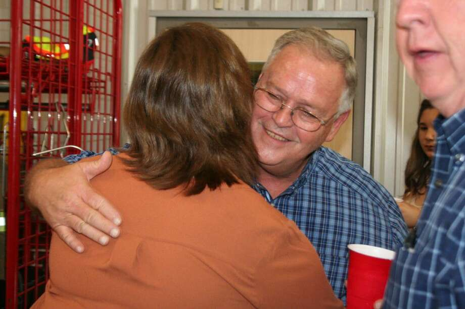 Guy Hancock hugs a guest at the Emergency Services Department dual retirement celebration Tuesday, Aug. 30.
