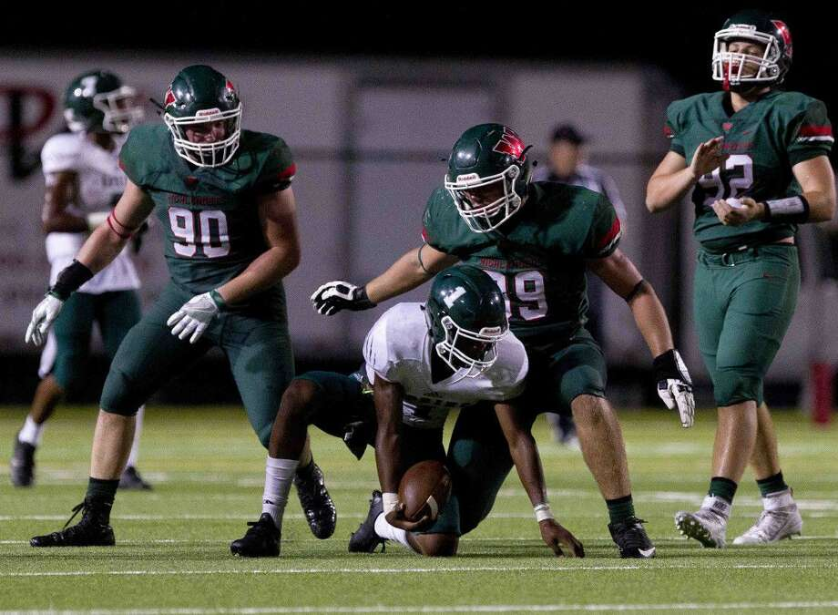 The Woodlands defensive lineman Michael Purcell (99) stands over Spring quarterback Eric Spencer Jr. (1) after a tackle during the third quarter of a non-district high school football game Thursday. Go to HCNpics.com to view more photos from the game.