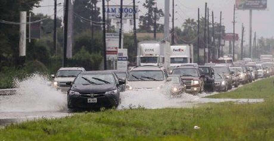 Drivers navigate around floodwaters Aug. 15 on the Interstate 45 northbound service road near Texas 242 following heavy rains in the area. Photo: Michael Minasi