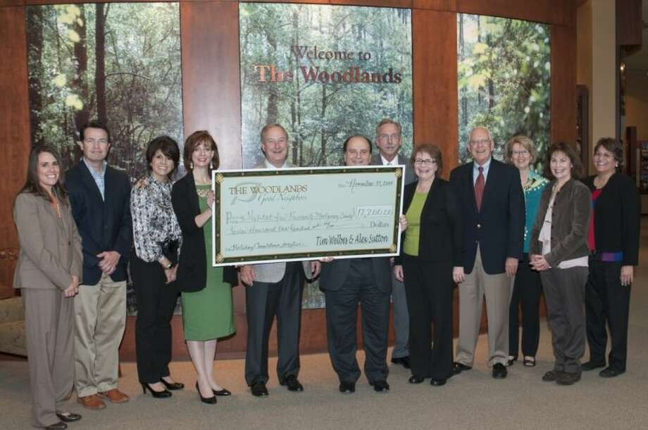 The Woodlands Development Company recently presented a $12,200 donation to Habitat for Humanity Montgomery County (HFHMC) as a result of the 2012 Holiday Countdown promotion. Pictured left to right: Jeanne Toth, manager of Relocation and Realtor Relations for TWDC; Eric Hird, board member, HFHMC; Patricia Brown, board member, HFHMC; Kimberly Lacayo, board member, HFHMC; Larry Abston, board member, HFHMC; Ron Brandt, Board member, HFHMC; Tim Welbes, co-president of TWDC; Barbara Smith, executive director, HFHMC; Russ Palmore, board member, HFHMC; Calleen McFerren, manager of The Woodlands Information Center; Susan Vreeland-Wendt, director of Marketing TWDC; and Lorrie Parise, marketing manager TWDC. Photo: Ted Washington