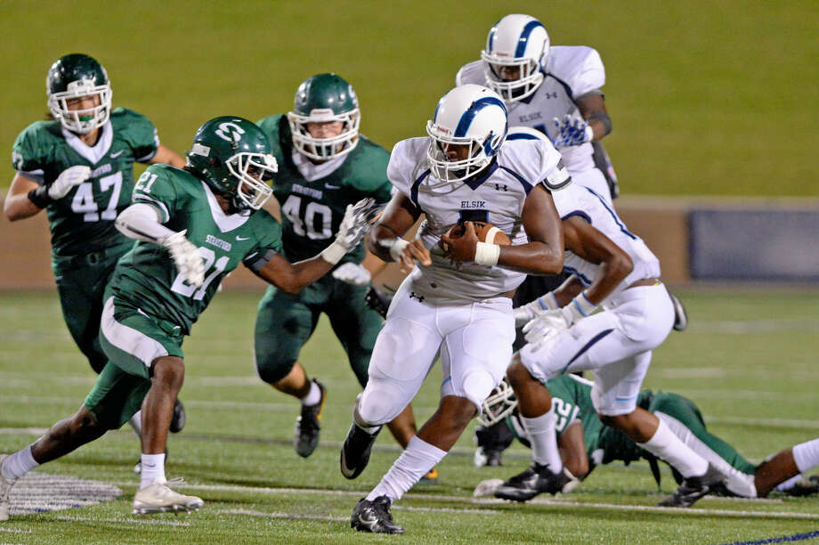 Quarterback Isaiah Ibeto (5) of Elsik runs for a four-yard gain and a first down as Stratford's Kendrick Dooley closes in during the third quarter of a high school football game between Stratford and Elsik on September 1, 2016 at Tully Stadium, Houston, TX. Photo: Craig Moseley