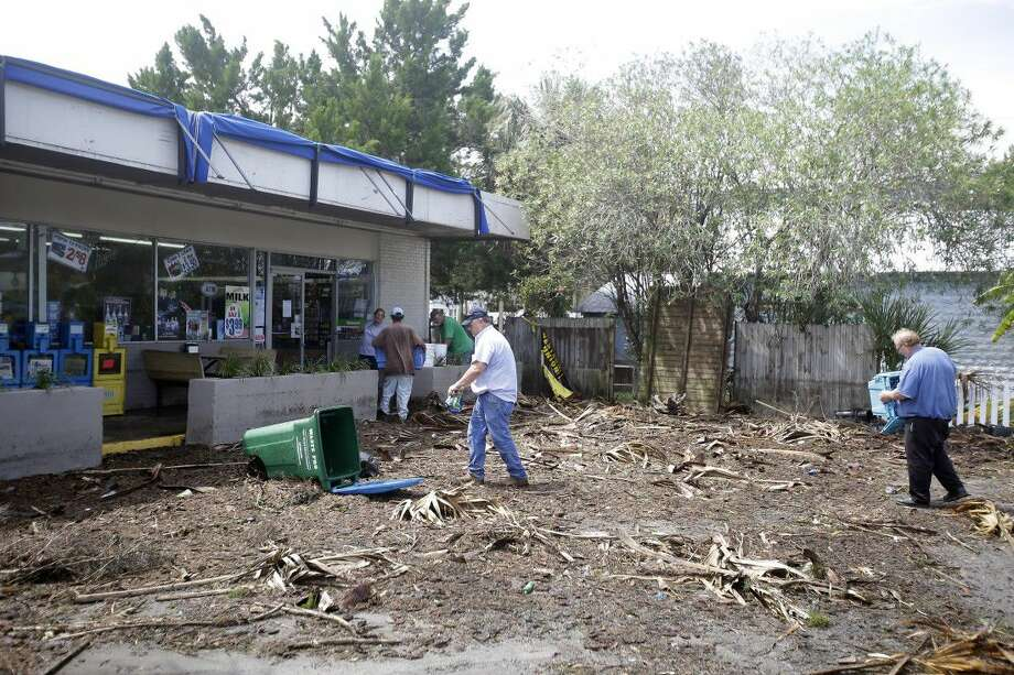 Workers clean up debris, caused by Hurricane Hermine, in the parking lot in front of a convenience store Friday in Cedar Key, Fla. Hermine was downgraded to a tropical storm after it made landfall.
