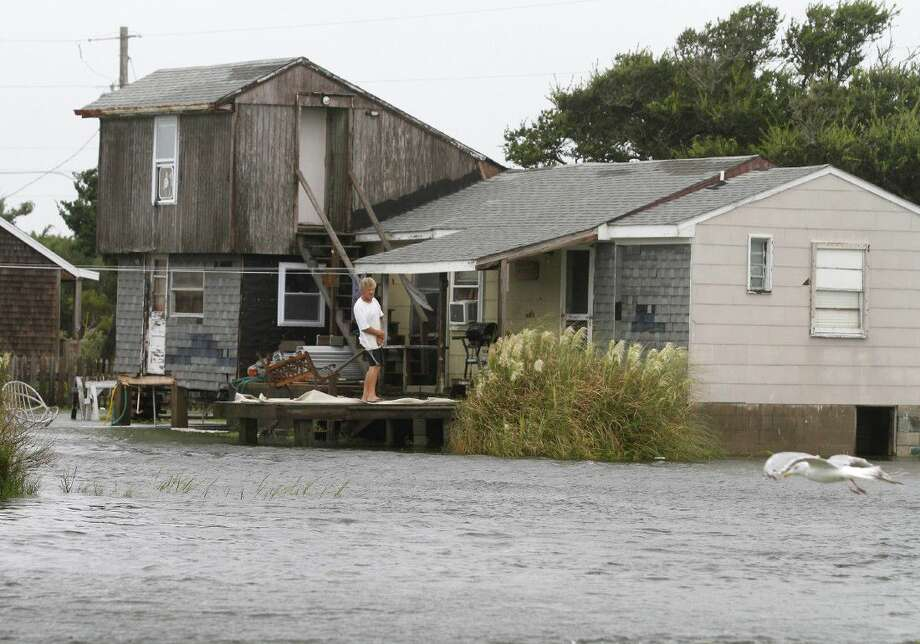 A unidentified man watches the rising water from his home in Hatteras, N.C., Saturday after Tropical Storm Hermine passed the Outer Banks. The storm is expected to dump several inches of rain in parts of coastal Virginia, Maryland, Delaware, New Jersey and New York as the Labor Day weekend continues.