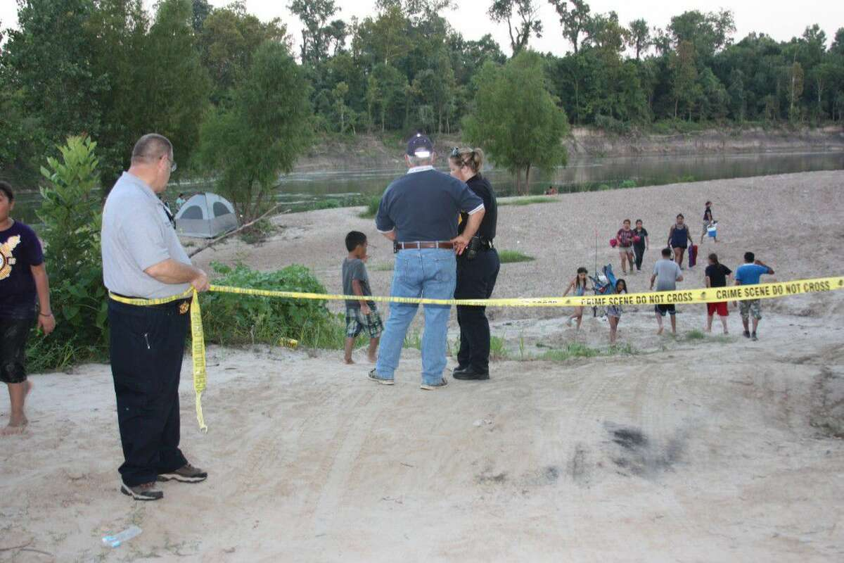 The Liberty County Sheriff's Office set up a makeshift perimeter about a quarter-mile from where a single-propeller plane went down Saturday night in the Trinity River near Moss Hill. Two people on the plane were killed.