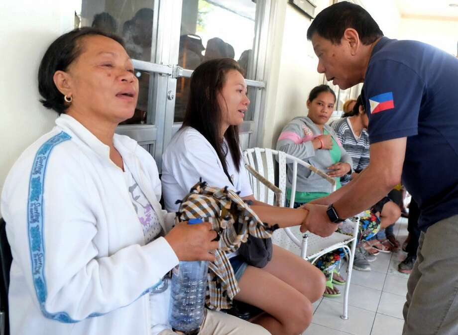 "Philippine President Rodrigo Duterte, right, comforts a victim outside a hospital where people injured in Friday's explosion at a night market were brought in in Davao city, his hometown, Saturday in southern Philippines. Duterte declared a nationwide ""state of lawlessness"" Saturday after suspected Abu Sayyaf extremists detonated a bomb at the market."