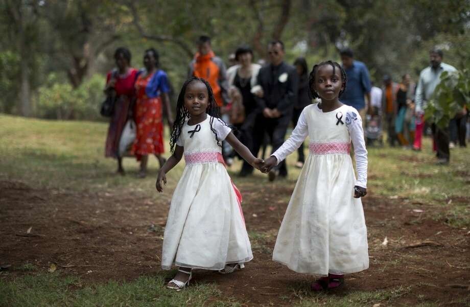 Gloria, 4, left, whose father Christopher Chewa was killed in the Westgate Mall attack, walks with her cousin Miriam, 6, right, and other families of the victims to lay flowers and remember at the Amani Garden memorial site in the Karura Forest in Nairobi, Kenya Sunday, Sept. 21, 2014. Kenya is marking one year since four gunmen stormed the upscale Westgate Mall in Nairobi, killing 67 people, and a memorial plaque with the names of the victims was unveiled at the popular forest on the edge of the city.