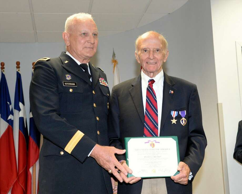 A representative of the United States Army presents James Duncan with the Purple Heart at the Tracy Gee Community Center in recognition of Duncan's service during the Korean War on Sept. 1. Photo: Craig Moseley
