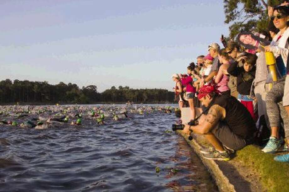 Triathletes swim during this year's Ironman Texas triathlon in Lake Woodlands as spectators watch at Northshore Park Saturday. Athletes began with a 2.4-mile swim, followed by a 112-mile bike ride and finished with a 26.2-mile run. To view or purchase this photo and others like it, visit HCNpics.com. Photo: Staff Photo By Ana Ramirez / The Conroe Courier/ The Woodland