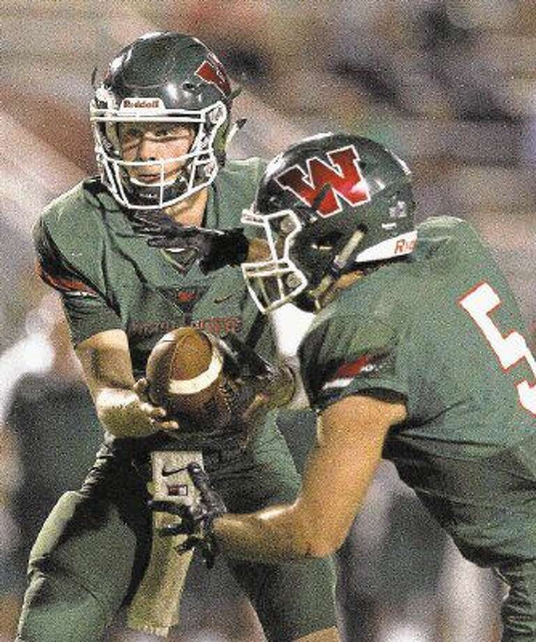 The Woodlands quarterback Eric Schmid (3) hands the ball off to running back Carlos Ramos (5) during the fourth quarter of a non-district high school football game Thursday at Woodforest Bank Stadium in Shenandoah.