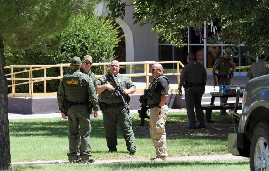 United States Border Patrol officers and Texas Department of Public Safety officers secure the perimeter around Alpine High School, Thursday in Alpine. A 14-year-old girl died of an apparent self-inflicted gunshot wound after shooting and injuring another female student Thursday inside the school, according to the local sheriff.