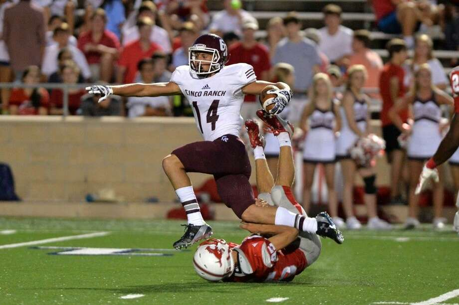 Cinco Ranch's Brant Kuithe hurdles a Memorial defender during a 41-yard reception during their 2015 game at Tully Stadium. Kuithe scored three touchdowns Sept. 8 as the Cougars defeated Memorial 51-0. Photo: Craig Moseley