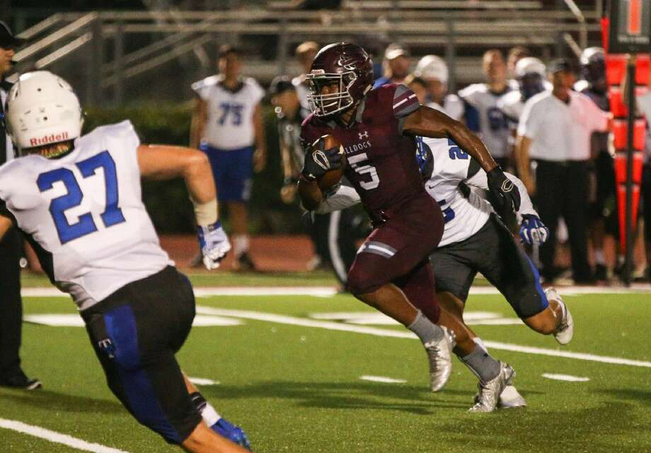 Magnolia's Anthony Johnson (5) runs the ball for a touchdown during the first half of the varsity football game against Katy Taylor on Friday at Magnolia High School.