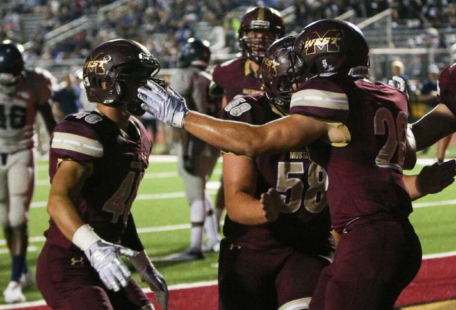 Magnolia West's Trey McGrew (20) celebrates with teammates after scoring a touchdown during the first half against Bryan on Friday at Magnolia West High School.