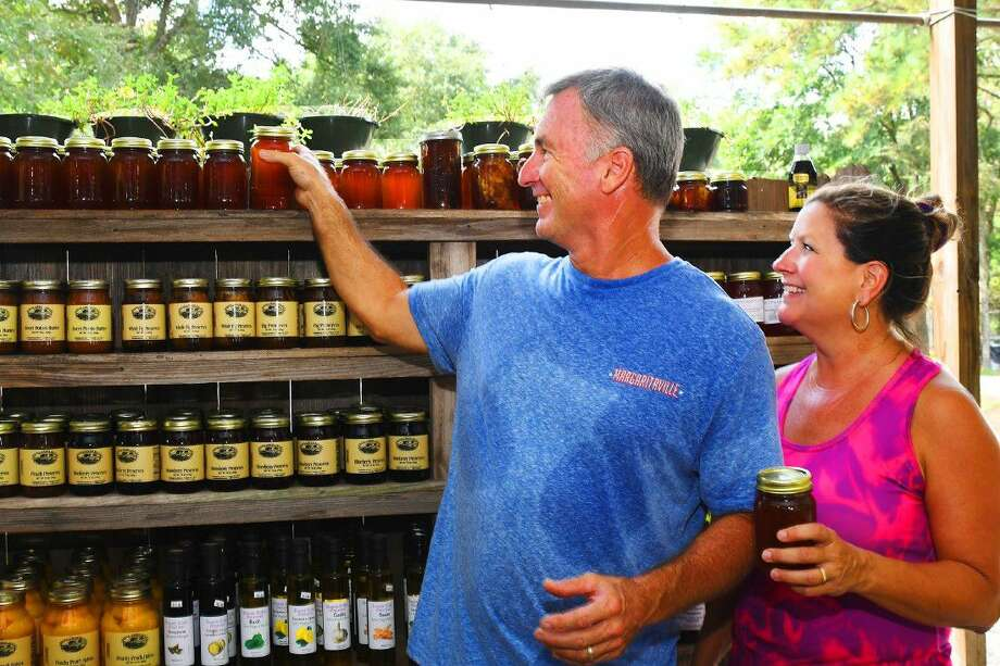 Mike and Stacey Watthuber stock the shelves with natural honey and perserves. The Theiss Farms Markets has been in the community for many decades. Stacey Theiss, now Stacey Watthuber, runs the Spring/Woodlands location with her husband Mike Watthuber. Theiss' parents, grandparents, and great-grand parents were all involved in farming for more than 150 years. Photo: Tony Gaines